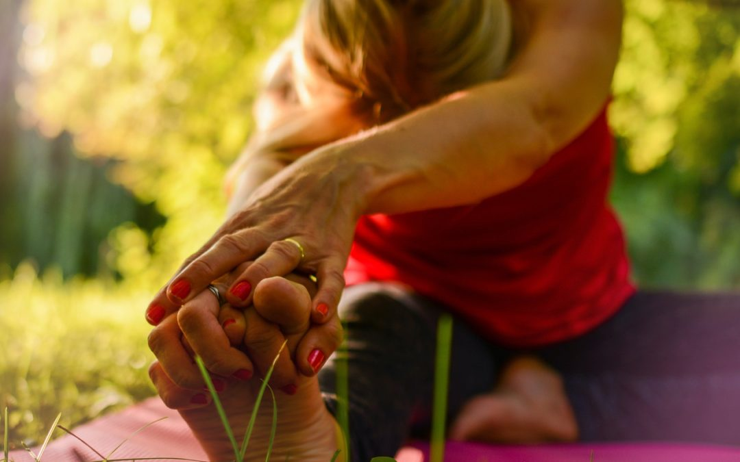 woman stretching with fingers interlocked into toes